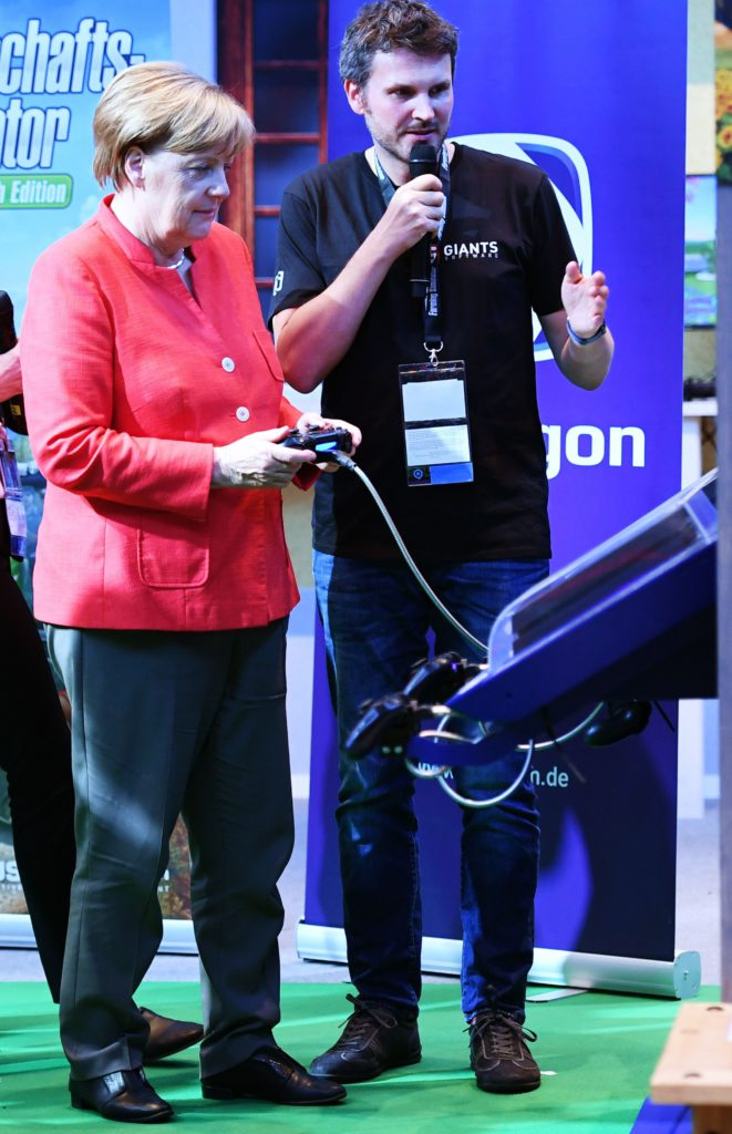 "German Chancellor Angela Merkel plays a farming game at the stand of Nintendo during the gaming fair ""gamescom"" in Cologne on August 22, 2017. / AFP PHOTO / PATRIK STOLLARZ / TT / kod 444"