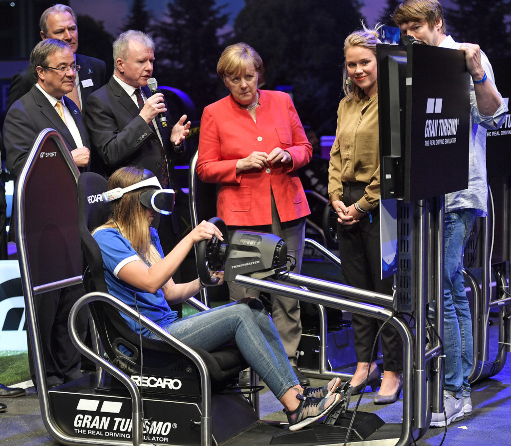 CEO of Sony Interactive Entertainment Jim Ryan explains to German chancellor Angela Merkel a virtual reality playstation game at the Gamescom fair for computer games in Cologne, Germany, Tuesday, Aug. 22, 2017. The leading European trade fair for digital gaming culture is the meeting point for global companies from the entertainment industry and the international gaming community. (AP Photo/Martin Meissner)