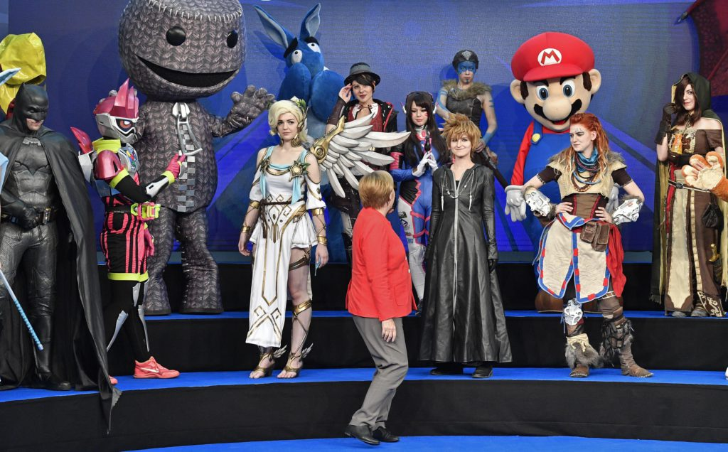 German chancellor Angela Merkel looks to cosplayers at the Gamescom fair for computer games in Cologne, Germany, Tuesday, Aug. 22, 2017. The leading European trade fair for digital gaming culture is the meeting point for global companies from the entertainment industry and the international gaming community. (AP Photo/Martin Meissner)